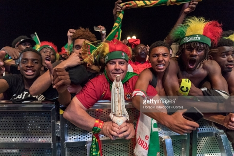 Portuguese supporters, one of them holding a statuette of the Virgin of Fatima, jubilate at their national team victory over France at the end of the match they watched for the final of UEFA Euro 2016 on a giant screen set up in Praca do Comercio on July 10, 2016 in Lisbon, Portugal
