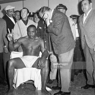 Sonny Liston holding up two fingers, gesturing second round knockout for his opponenet Cassius Clay, during his medical check prio the fight, Miami, USA (Harry Benson/Contour by Getty Images)