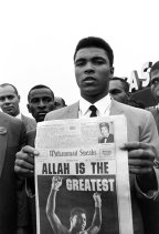 "Muhammad Ali, holds a ""Muhammad Speaks"" newspaper bearing his picture as he and followers leave the Las Vegas convention center after weigh-in ceremonies to defend his title against challenger Floyd Patterson, on Nov. 22, 1965 (AP Photo/Sal Veder)"