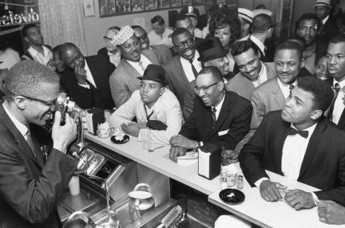 Malcolm X, left, is seen behind a soda fountain photographing Muhammad Ali, sitting at counter surrounded by jubilant fans after he beat Sonny Liston for the heavyweight championship of the world in Miami in 1964 (Bob Gomel, TIME & LIFE Pictures/Getty Images)